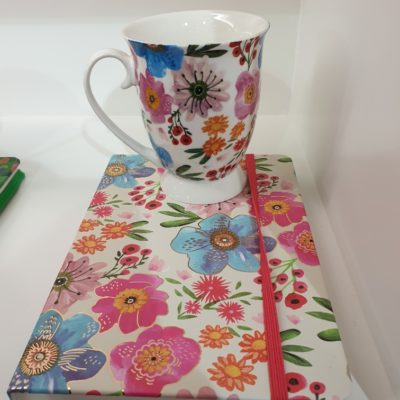 mug and notebook set with colourful flowers spread across white base mug and notebook