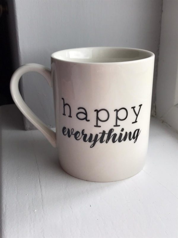 cream mug with happy everything written in black