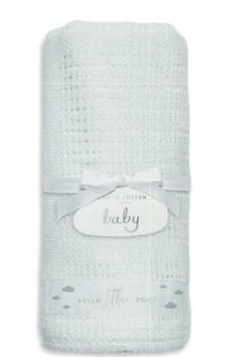white knitted cotton blanket rolled up with a white ribbon bow