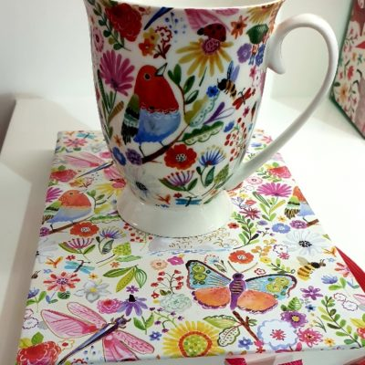Swan Garden Design Mug and Notebook Set. Swan Garden design is a vibrant colourful display of birds, butterlfies and flowers on a white base mug and notebook