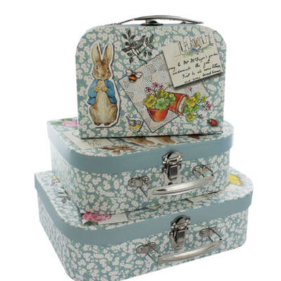 Small, medium and large suitcases stacked. Light blue with white florals and beatrix potter bunny