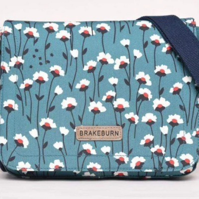 Brakeburn Emily Saddle Bag. Teal base colour with white and red floral design. Navy strap and brown brakeburn logo