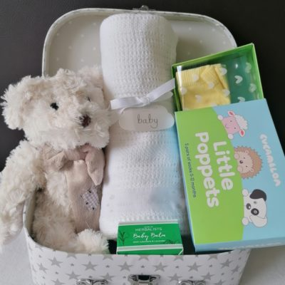 white and silver star suitcase with a range of baby gift options including a wilberry cream classic teddy bear, white cotton blacnket, Dublin herbalist Baby Balm and Little poppets box of baby socks