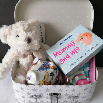 silver and white suitcase containing wilberry classic cream teddy bear, shannonbridge pottery money box and mommy and me cucamelon box of baby socks