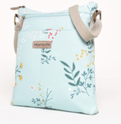 brakeburn cross over handbag, sky blue base colour with green leaf details and yellow and red flowers, fawn strape and fawn zip detail