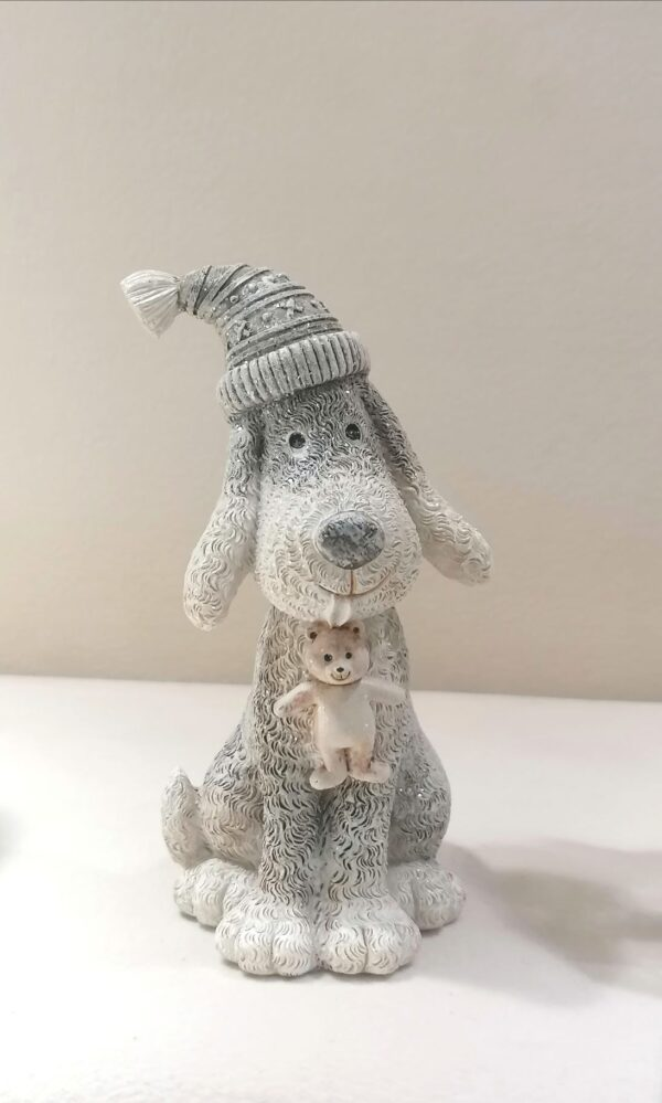 Grey and white Christmas dog carrying Teddy Bear in this mouth